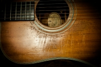 Years of strumming , picking and pounding have worn away at the sound hole.