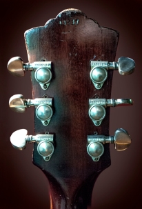 The original tuning pegs were upgraded 30 years ago but you can still see the drill holes from the original hardware. AT the top of the headstock the serial number is faded but still visible.