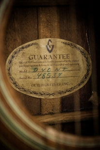 "Seen through the sound hole; The original Guild certificate ""Guarantee"" . The model and serial number are hand written."